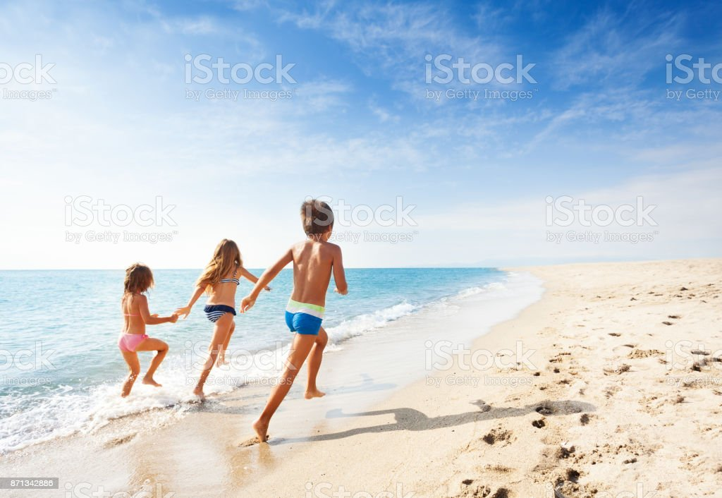 Kids running along beach during summer vacation stock photo