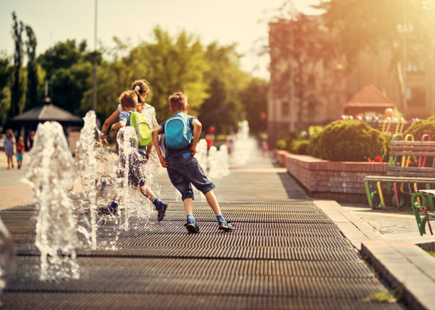 Kids running between fountains on a hot summer day. stock photo