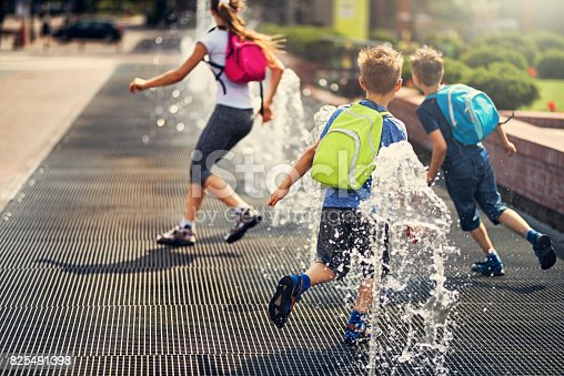 School children are having fun playing in the city fountains after school.