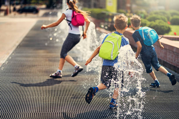 Kids running between fountains on a way from school stock photo