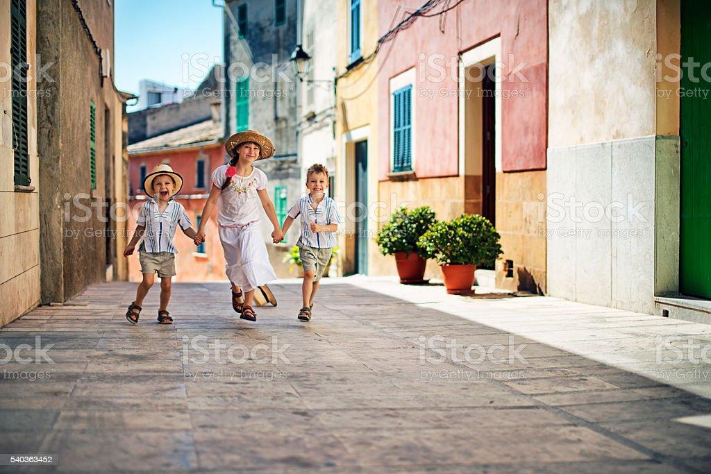 Kids running in beautiful mediterranean town. stock photo