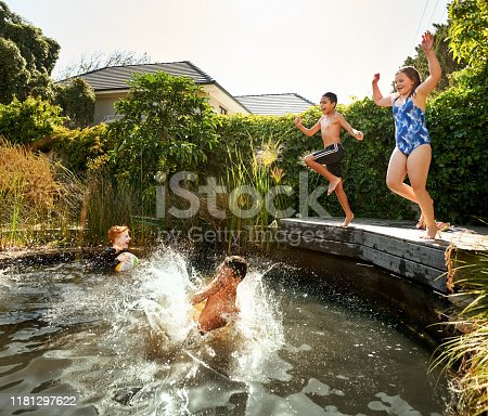 Shot of children jumping into an outdoors pool on a summer day