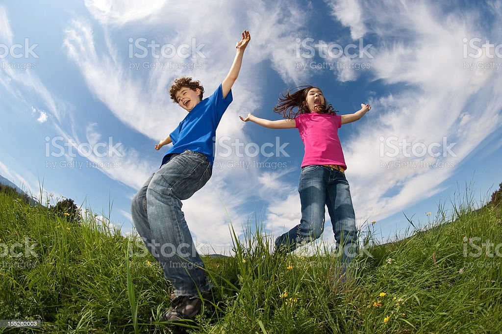 Kids running on green meadow royalty-free stock photo