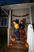 Full length portrait of excited children leaving house trick or treating on Halloween, shot with flash