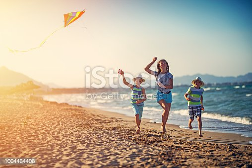 istock Kids running with kite on a beach 1004464406