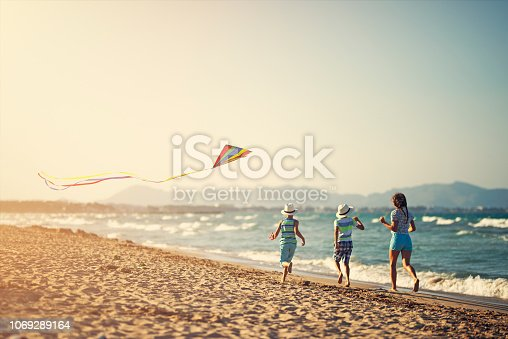 istock Kids running with kite on a beach 1069289164