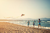 Three kids enjoying flying a kite on a beach. Brothers and sister are running and laughing.\nNikon D850