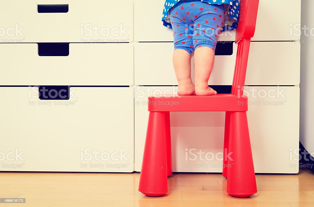kids safety concept- little girl climb on chair stock photo