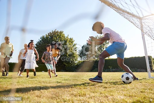 istock Kids scoring goal against dad during family football game 1045347692