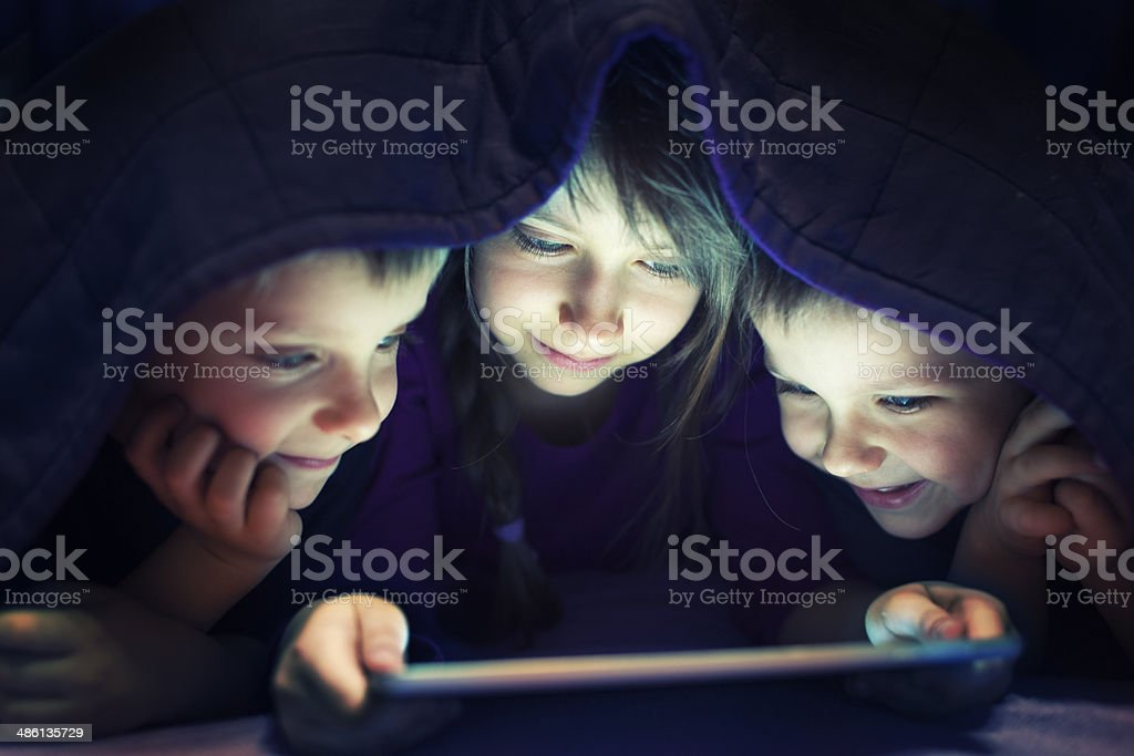 Kids secretly reading book on digital tablet stock photo