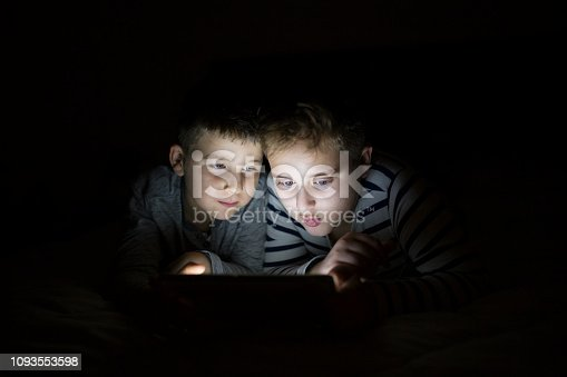 Kids secretly reading playing with digital tablet
