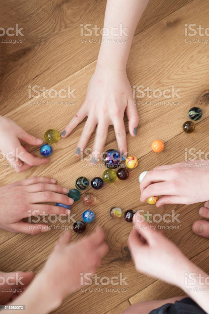 Kids setting up a game of marbles Busy children's hands scramble to select marbles for the next game.  Activity Stock Photo