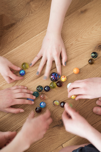 Kids Setting Up A Game Of Marbles Stock Photo - Download Image Now