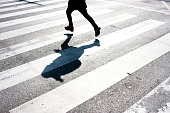 Blurry child's legs and kid's shadow with a backpack, on zebra crossing while running over the street in black and white
