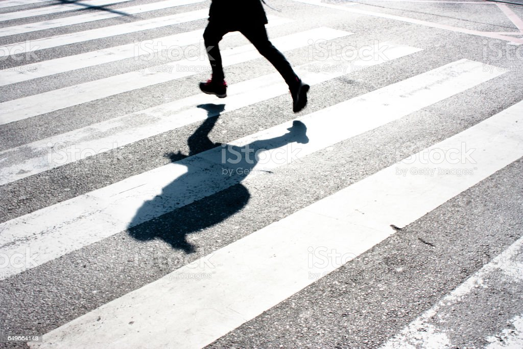 Kid's shadow on zebra crossing stock photo