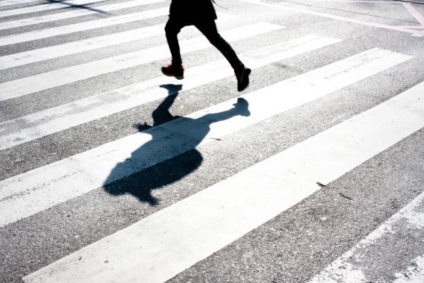 Kid's shadow on zebra crossing stock photo
