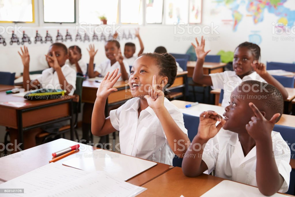 Kids showing hands during a lesson at an elementary school stock photo