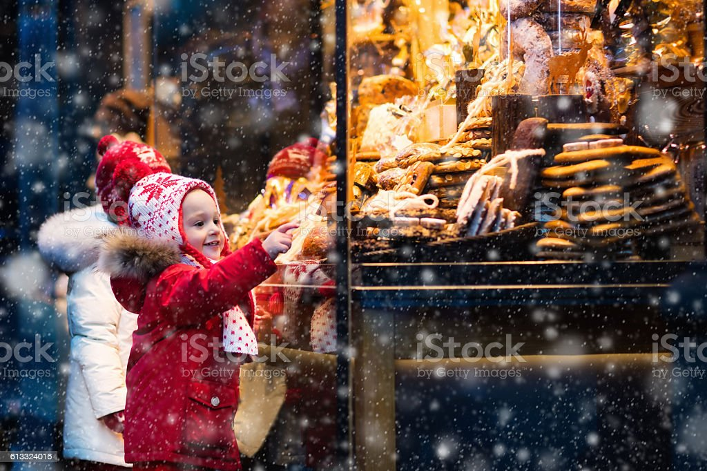 Kids siblings looking at candy and pastry on Christmas market stock photo