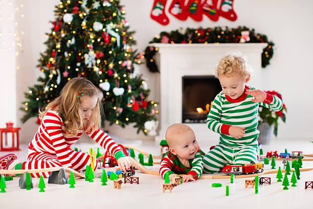 kids siblings playing with toy railroad on christmas morning - festzugskleidung stock-fotos und bilder