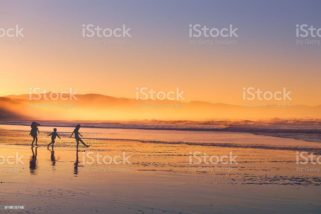 los niños jugando y divirtiéndose de silueta en la playa al atardecer - foto de stock