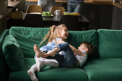 Kids Sister And Brother Laughing Tickling On Sofa Playing ...
