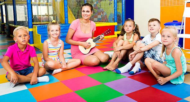 kids sitting around teacher with small guitar - ukulele songs stock-fotos und bilder