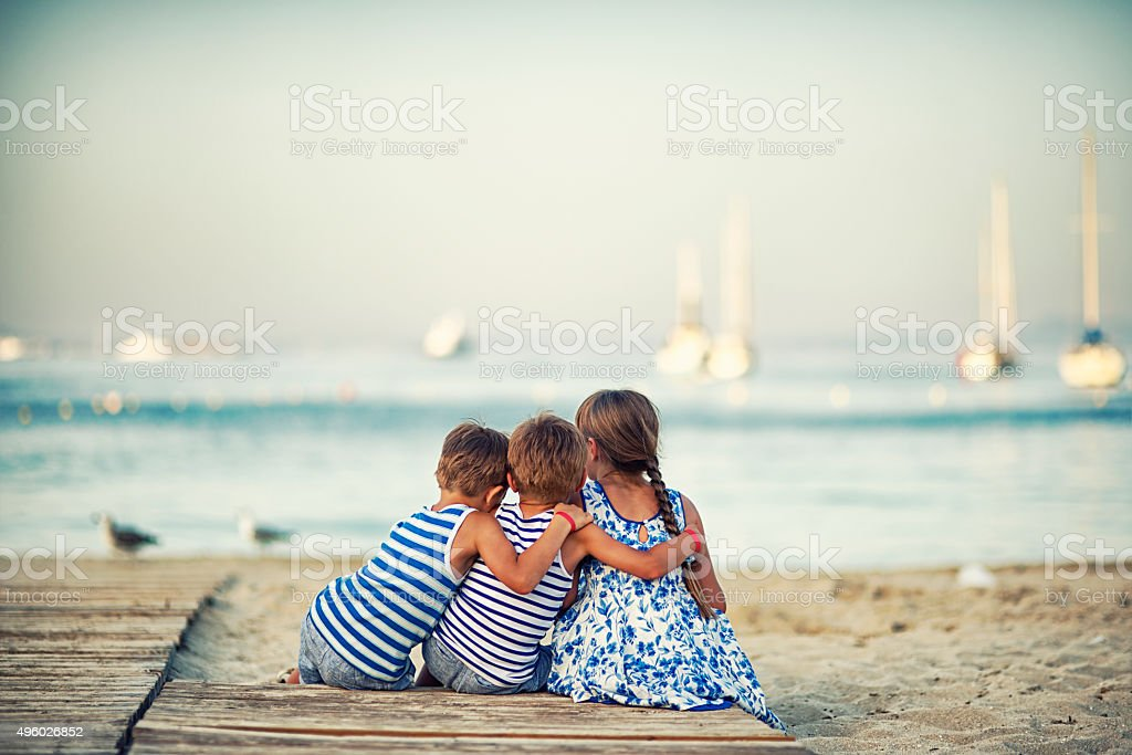 Kids sitting at the beach at the evening and embracing stock photo