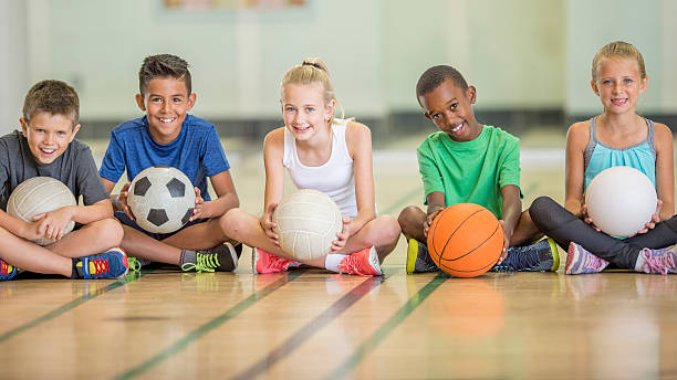 kids sitting at the gym - volleyball sport stock photos and pictures