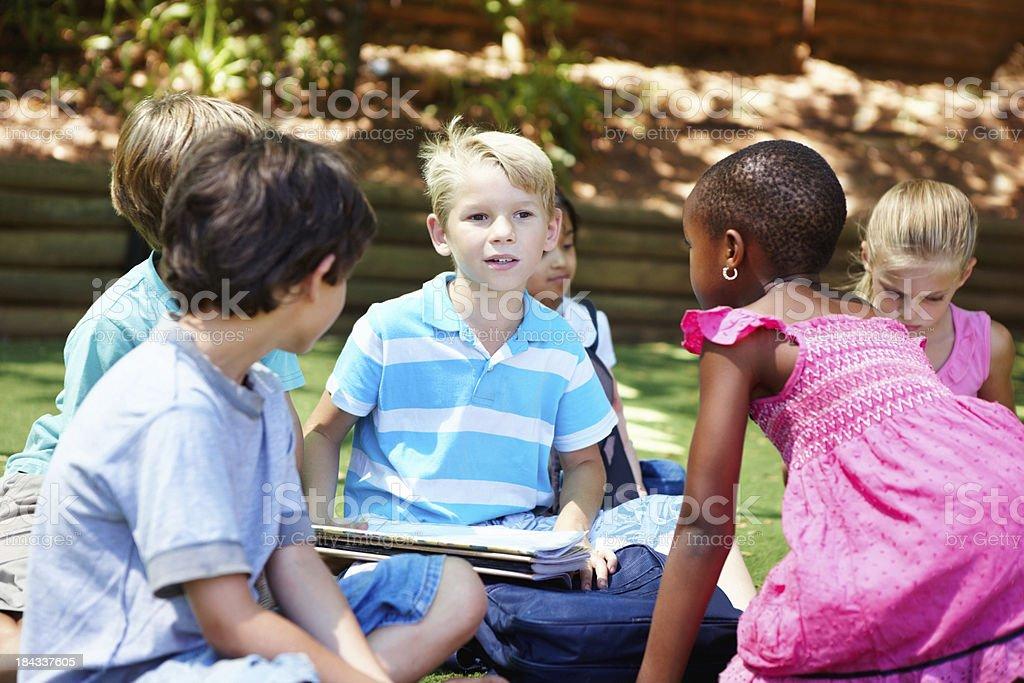 Kinder sitzen auf Gras und lernen – Foto