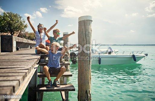 Kids enjoying Garda Lake vacations. Kids are cheering sitting at pier. Nikon D850