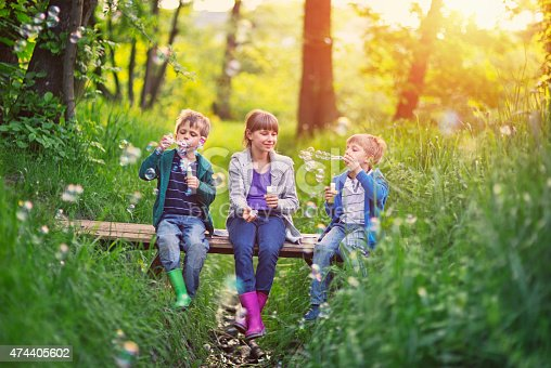 618034312 istock photo Kids sitting on little bridge and blowing bubbles 474405602