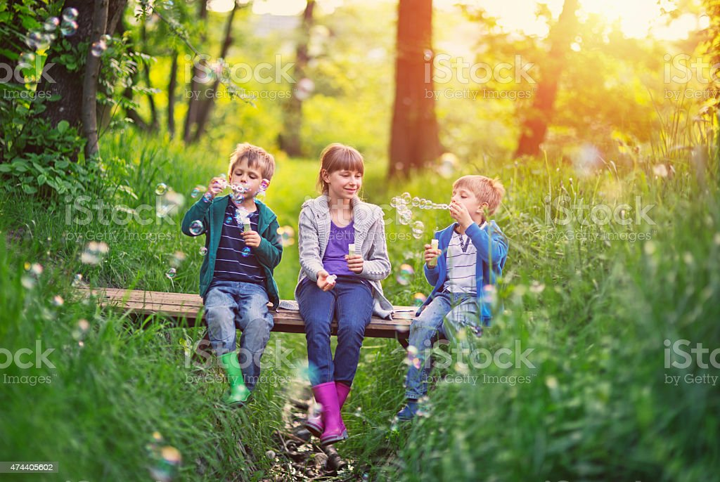 Kids sitting on little bridge and blowing bubbles stock photo
