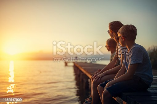 Three kids enjoying sunset at Garda Lake. Kids are sitting on a lake pier. Nikon D850