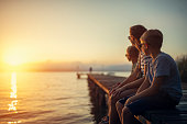 Three kids enjoying sunset at Garda Lake. Kids are sitting on a lake pier.\nNikon D850
