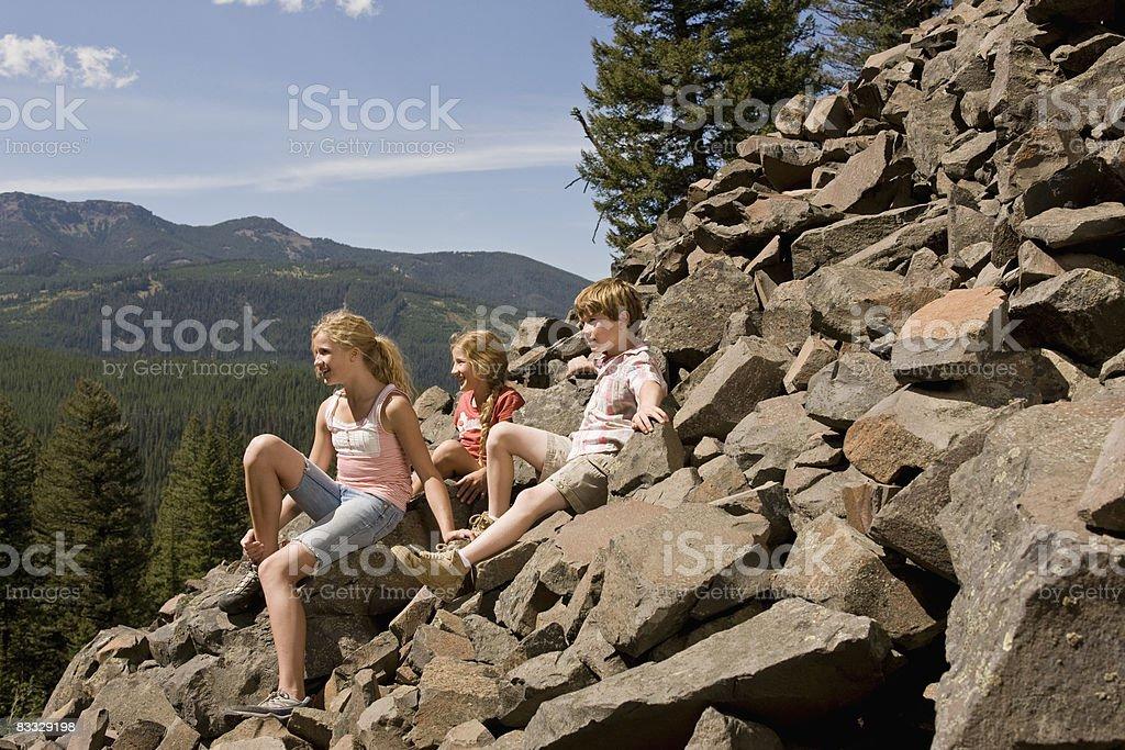 Bambini sedersi sulla roccia con vista sulle montagne foto stock royalty-free