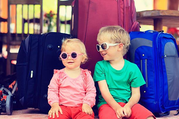 kinder sitzen auf den koffer für reisen - sonnenbrille kleinkind stock-fotos und bilder