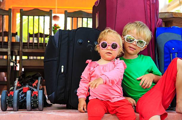 kinder sitzen auf den koffer für reisen - kleinkind busy bags stock-fotos und bilder
