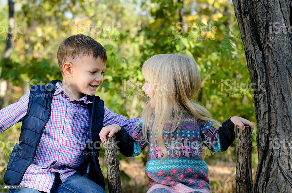 Kids Sitting on the Fence Holding on the Brace - Royalty-free 2015 Stock Photo