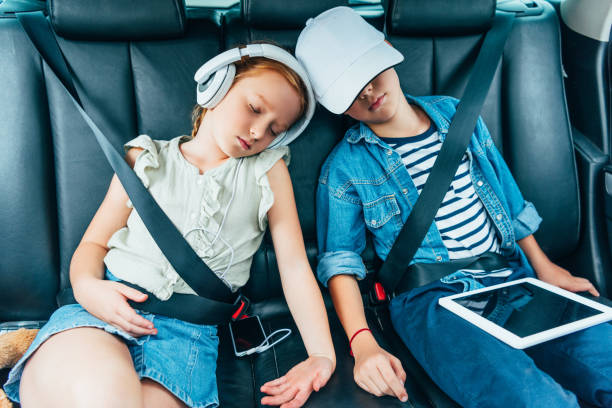 kids sleeping on backseats of car stock photo