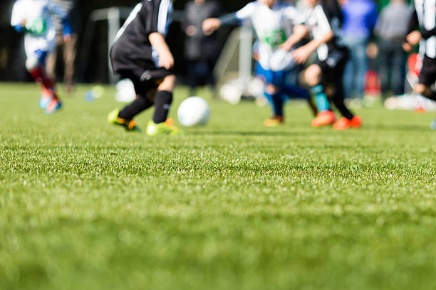 Kids soccer blur Picture of kids soccer training match with shallow depth of field. Focus on foreground. turf stock pictures, royalty-free photos & images