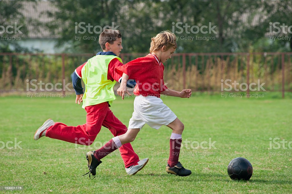 Kids soccer game with players chasing ball stock photo