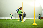 Group of children on soccer training. Kicks soccer ball around yellow cones.