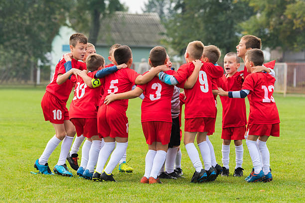 kids soccer team in huddle - équipe sportive photos et images de collection
