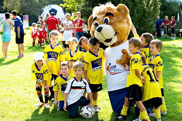 mascotte de l'équipe de football avec les enfants - mascotte photos et images de collection
