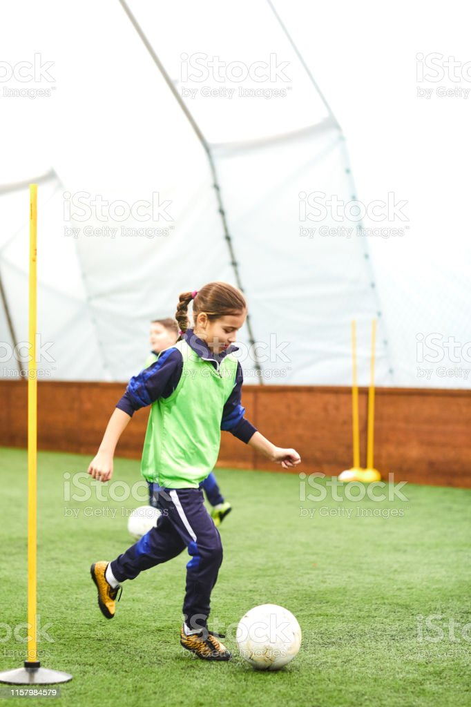 Cute girl training with ball on soccer training.