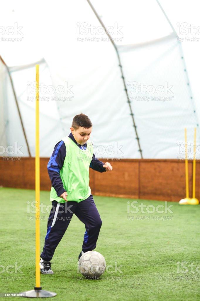 Cute boy training with ball on soccer training.