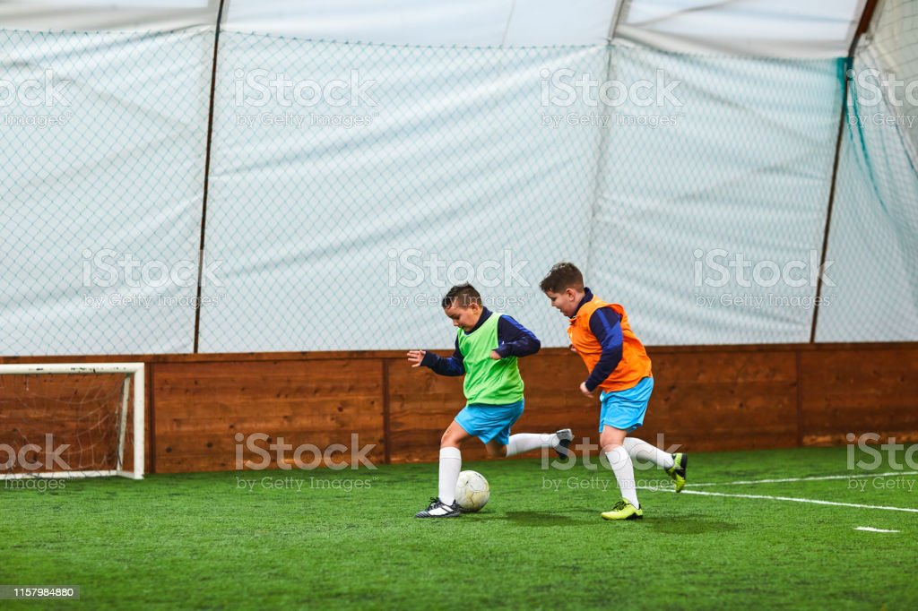 Two boys playing indoor soccer.