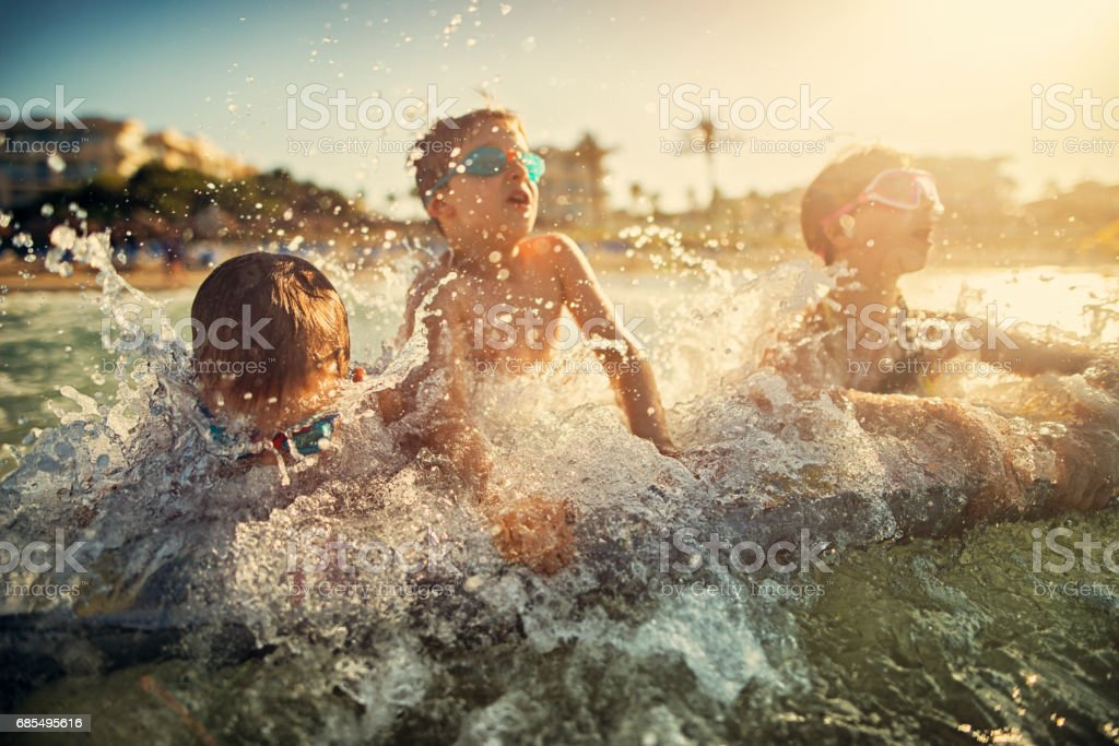 Kids splashed by sea wave stock photo