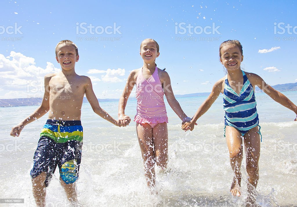 Kids splashing and playing in the ocean royalty-free stock photo