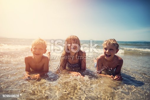Brothers and sister are having fun in sea. Kids aged 7 and 11 are lying on the beach and being splashed by waves.\n